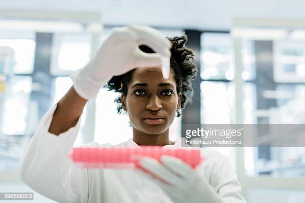 Black female scientist putting flask in container