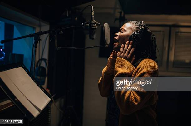 black female singer singing into microphone in recording studio - recording studio stock pictures, royalty-free photos & images