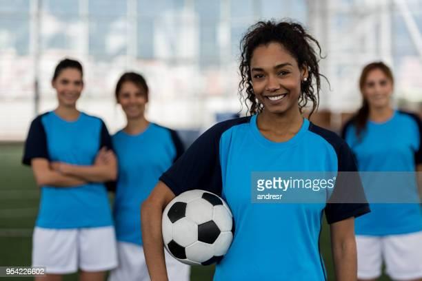 capitano di calcio femminile nero che tiene la palla guardando la telecamera sorridente - calciatore foto e immagini stock