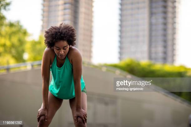 black fitness woman taking a break after workout outside - hand on knee stock pictures, royalty-free photos & images