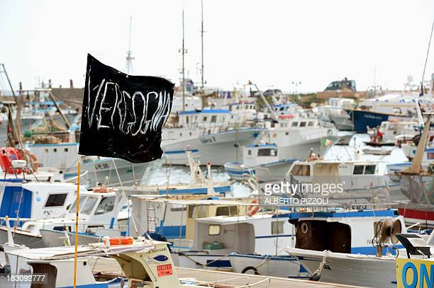 A black flag reading Shame in Italian flies in the Lampedusa harbour on October 4 2013 a day after a boat with migrants sank killing more than...