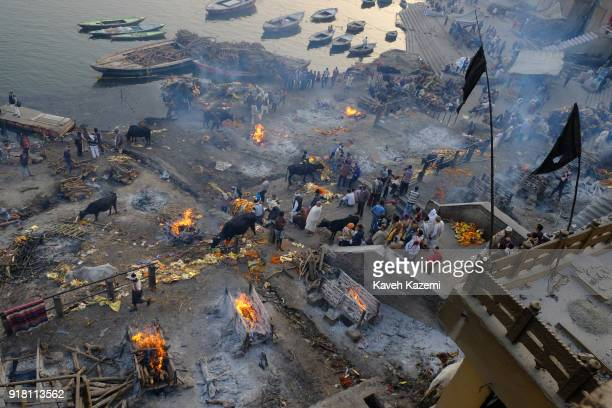 Black flags hang high from Manikarnika Ghat durning mass cremation ceremony with multiple burning pyres seen on the ground on January 28, 2018 in...