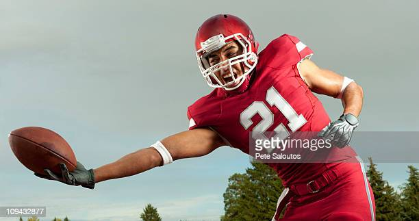 black football player catching football - safety american football player stock pictures, royalty-free photos & images