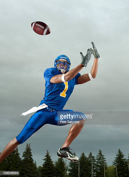 black football player catching football player in mid-air - safety american football player stock pictures, royalty-free photos & images