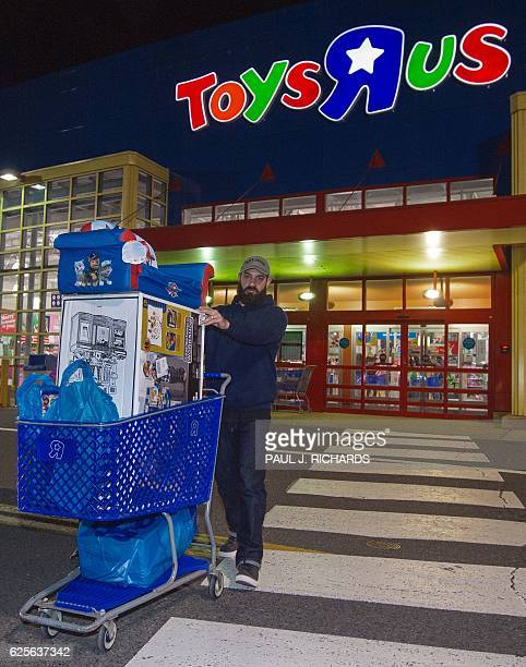 A Black Friday shopper is seen leaving a ToysRUS store with a full shopping cart in Fairfax Virginia on November 24 2016 / AFP / PAUL J RICHARDS