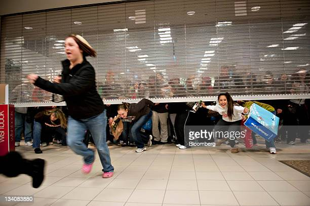 Black Friday shoppers duck under the opening door of a Sears store at Simon Property Group Inc's Great Lakes Mall in Mentor Ohio US on Friday Nov 25...