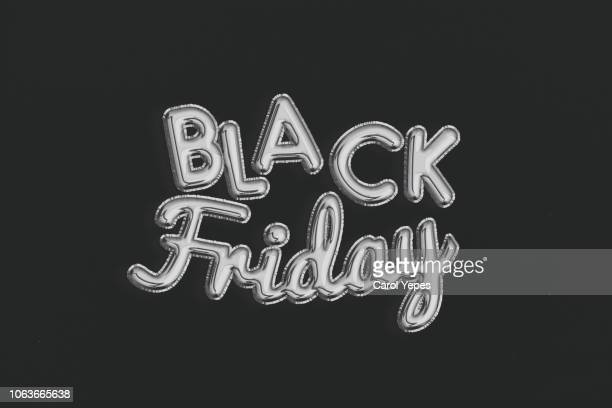 black friday silver balloon on black background - black friday stock photos and pictures
