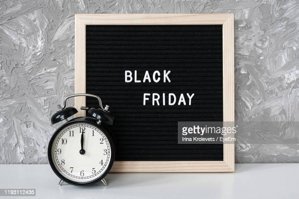 black friday text with alarm clock on table - capital letter stock pictures, royalty-free photos & images