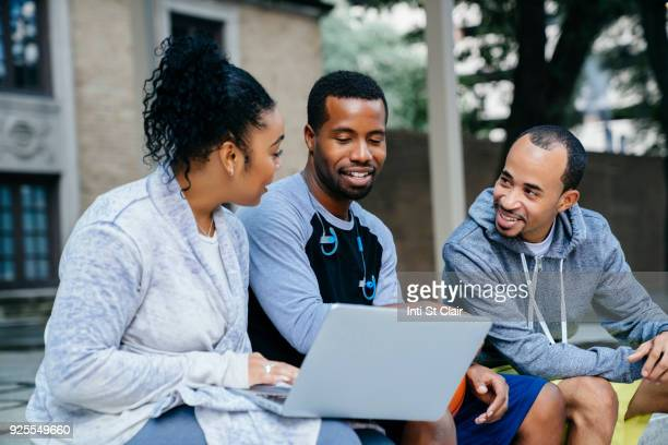 Black friends sitting outdoors using laptop