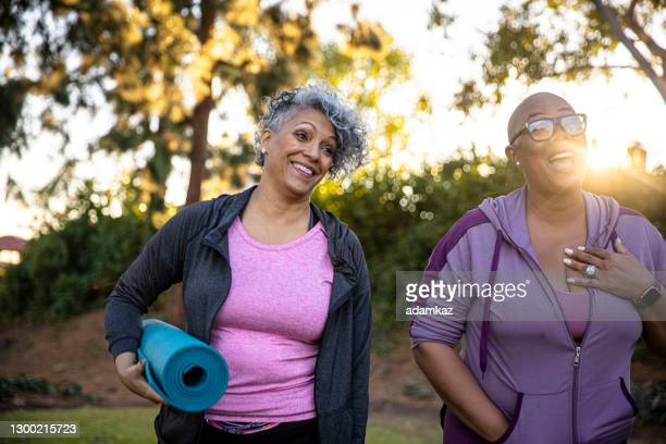 black friends walking away with her yoga mat - adamkaz stock pictures, royalty-free photos & images