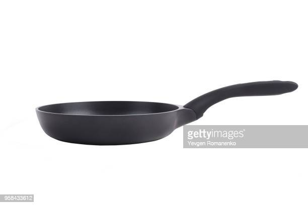 black frying pan with a non-stick teflon coating, isolated over the white background - ferro fundido - fotografias e filmes do acervo