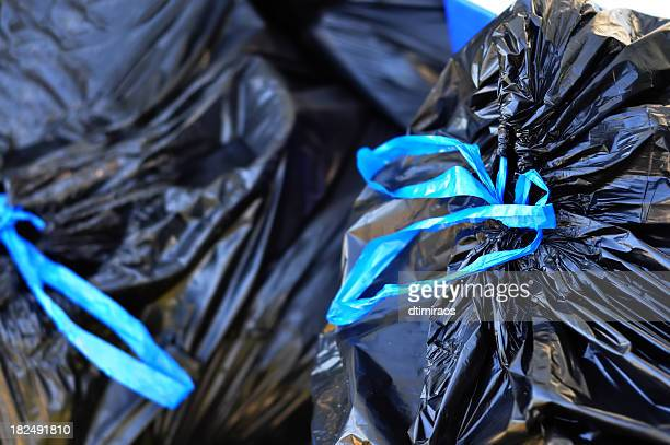 black garbage bags tied with blue strings - bin bag stock pictures, royalty-free photos & images