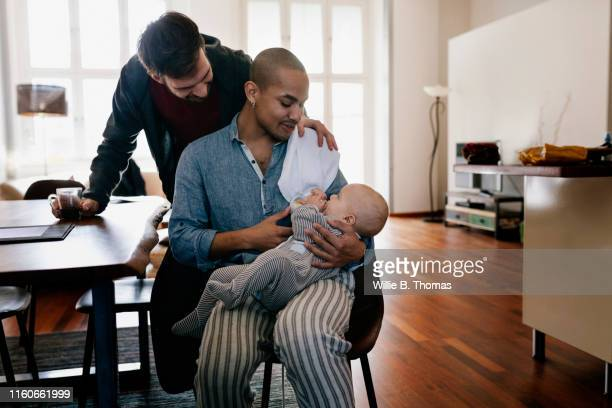 black gay father and partner feeding baby bottle - baby human age stock pictures, royalty-free photos & images