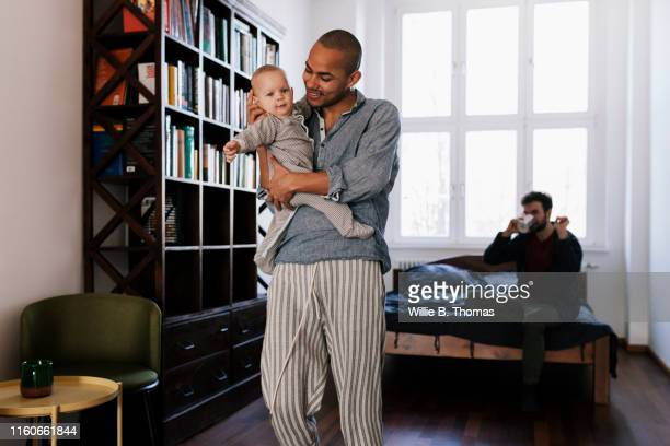black gay father leaving bedroom with son - printed sleeve stock pictures, royalty-free photos & images