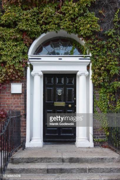 black georgian door surrounded by ivy with doorknob - ジョージア調 ストックフォトと画像
