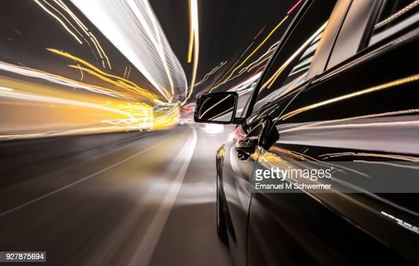 black german car drives fast on illuminated highway - vehicle mirror stock-fotos und bilder