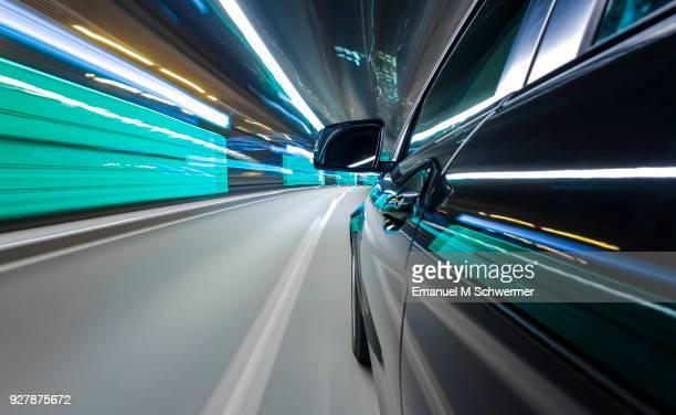 black German car drives through a modern tunnel