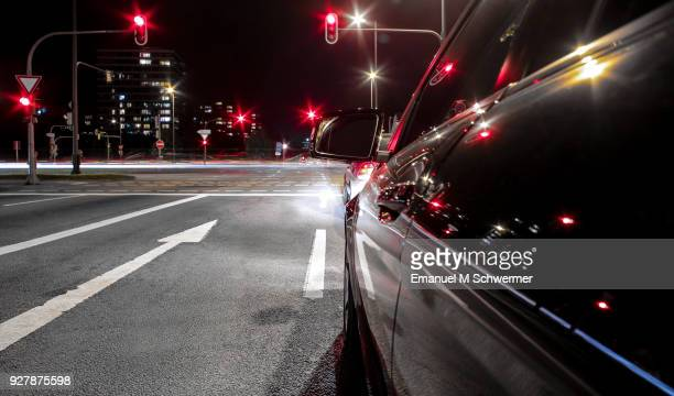 black German car drives through the city of Munich - stopping at red traffic lights