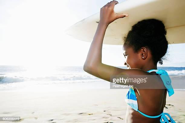 Black girl carrying surfboard on beach