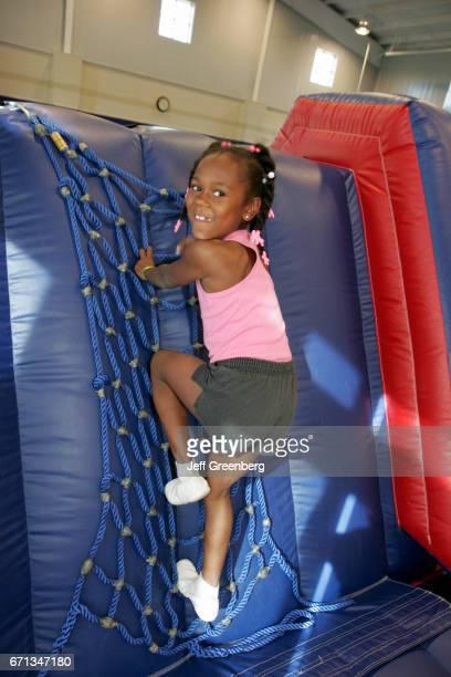 A Black girl climbing in a gymnastics class at Sportsplex