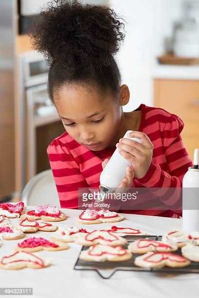 black girl decorating cookies - valentines african american stock pictures, royalty-free photos & images