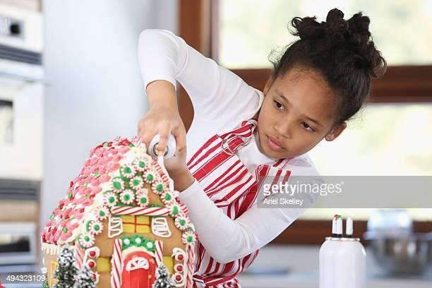 Black girl decorating gingerbread house