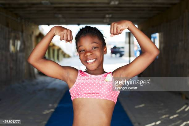 black girl flexing muscles outdoors - flexing muscles stock pictures, royalty-free photos & images