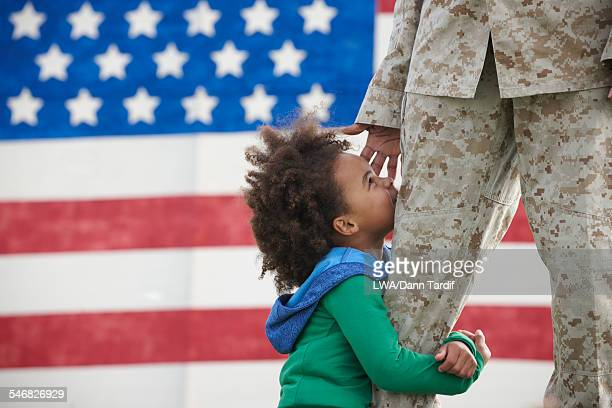Black girl hugging leg of returning soldier