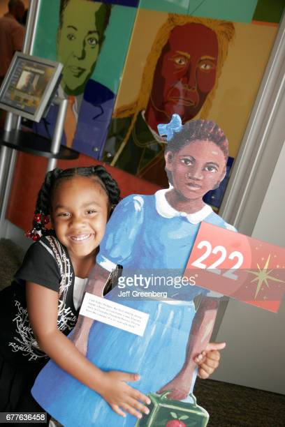 A Black girl hugs a Ruby Bridges cutout at the National Underground Railroad Freedom Center