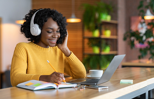 Black girl in headphones studying online, using laptop at cafe 1209049772