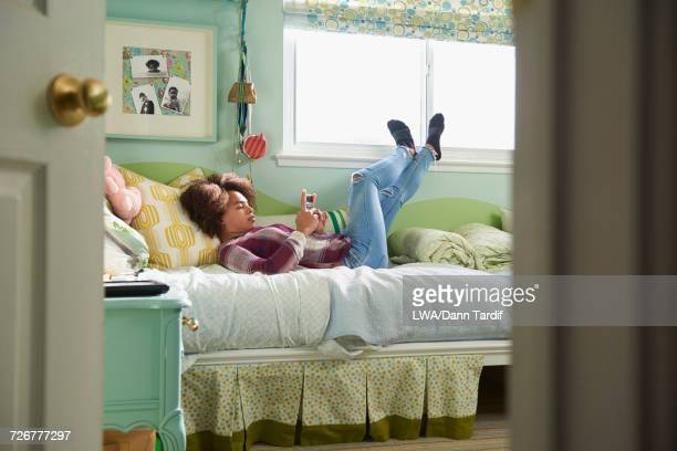 Black girl laying on bed texting on cell phone