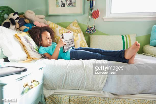 Black girl laying on bed using digital tablet