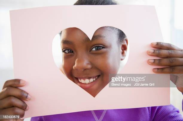 black girl looking through heart-shaped opening in paper - valentines african american stock pictures, royalty-free photos & images