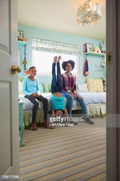 Black girl performing handstand near sisters in bedroom