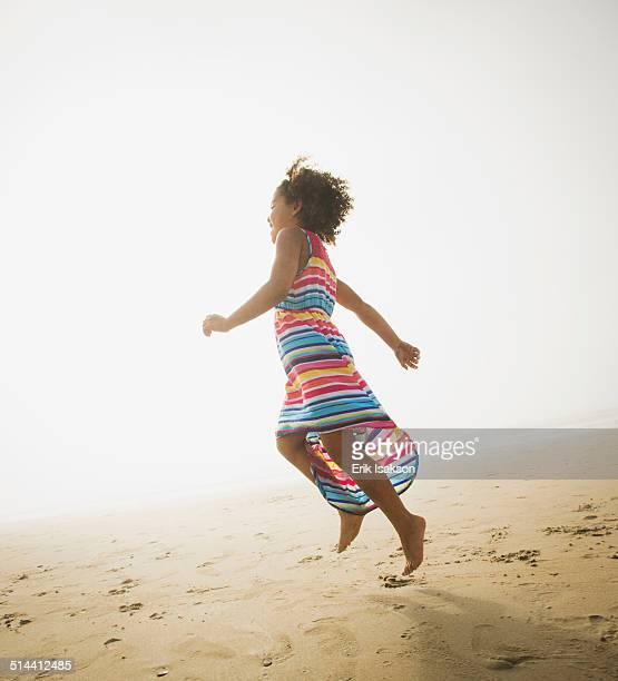 Black girl playing on beach