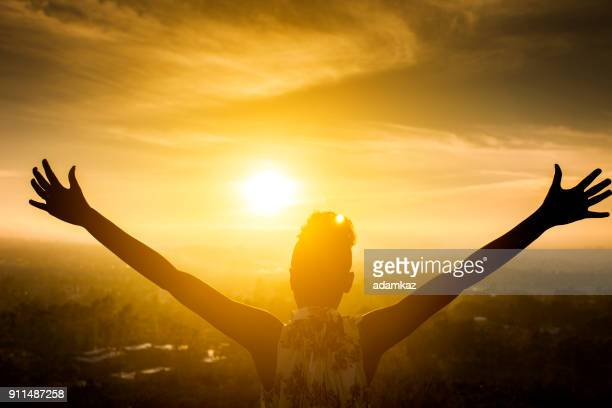 black girl raising arms over valley in sunset - praying stock pictures, royalty-free photos & images