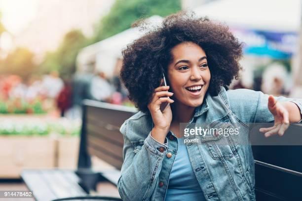 Fille noire, parler au téléphone sur un banc