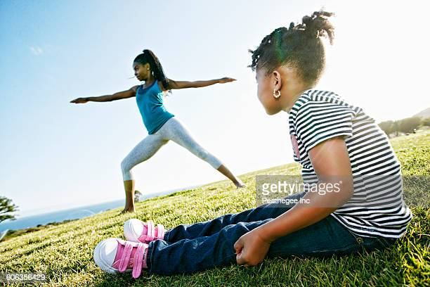 Black girl watching mother practicing yoga