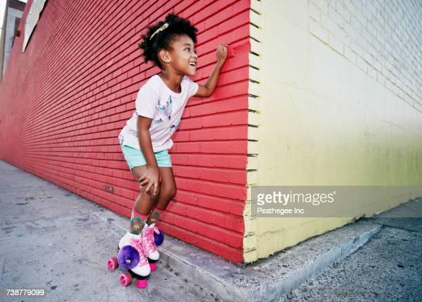 Black girl wearing roller skates peeking around corner