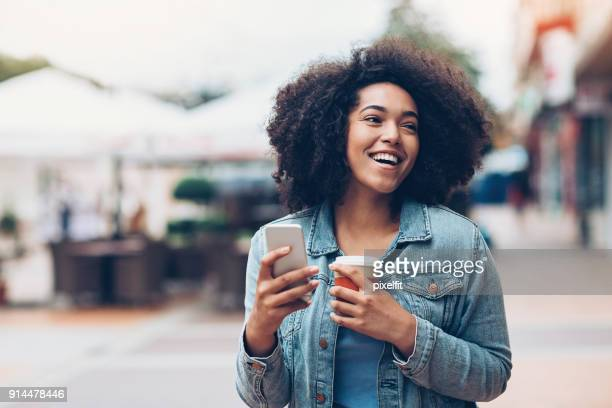 black girl with phone and coffee outdoors in the city - black jacket stock pictures, royalty-free photos & images