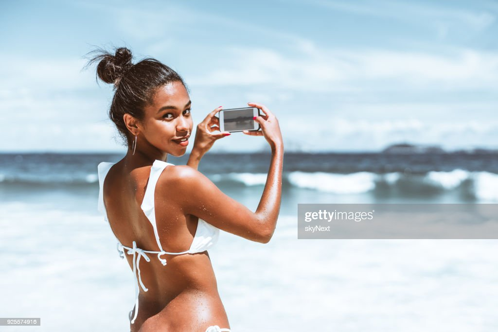 Black girl with smartphone on the beach