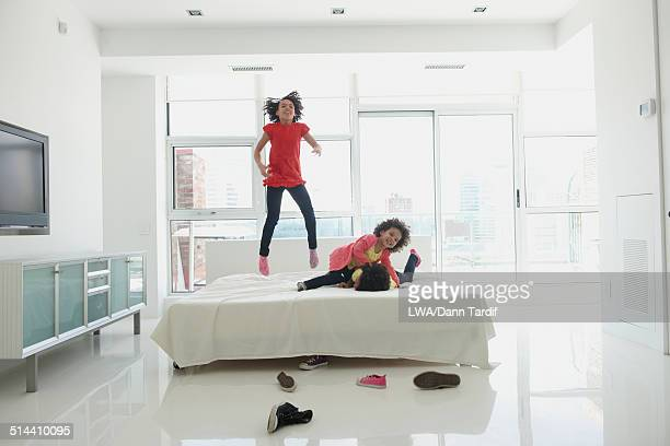 Black girls jumping on bed