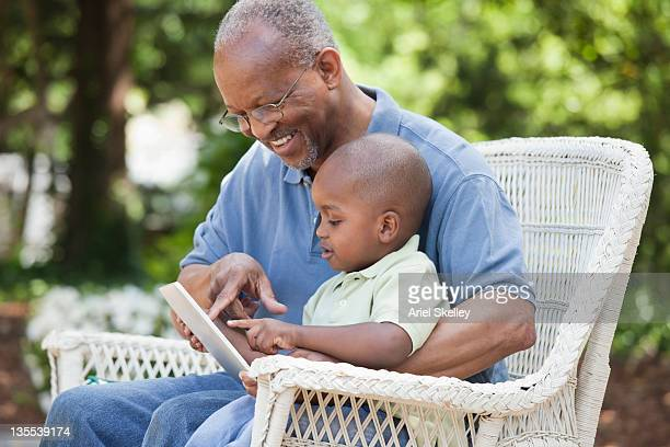 black grandfather and grandson using digital tablet - school cane stock photos and pictures