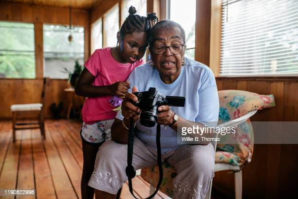 Black grandmother and granddaughter looking at photos