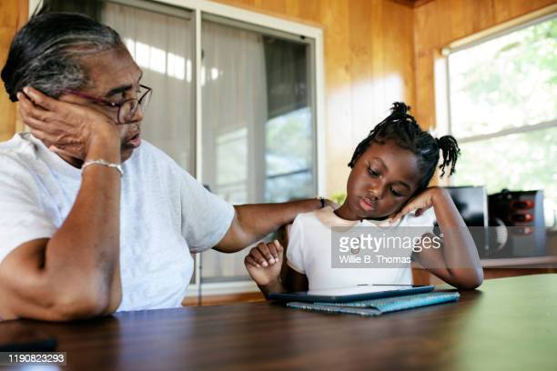 black grandmother  and granddaughter using digital tablet -  eラーニング ストックフォトと画像