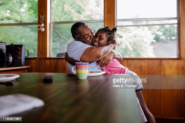 black grandmother hugging granddaughter - lifestyle stock pictures, royalty-free photos & images