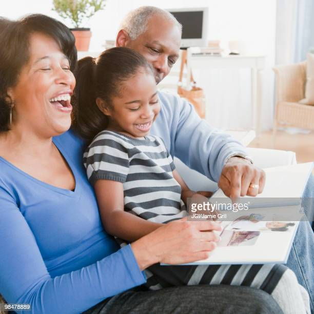 black grandparents looking at photographs with granddaughter - funny black girl ストックフォトと画像
