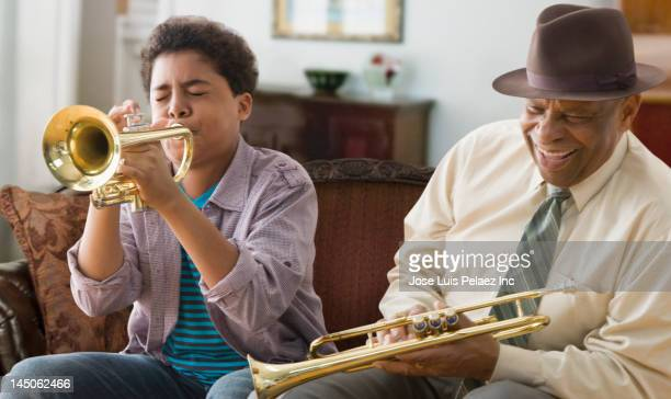 Black grandson and grandfather playing trumpet together