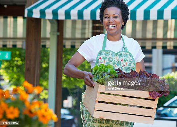 Black grocer carrying crate of lettuce