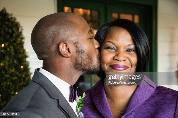 Black groom kissing mother at wedding